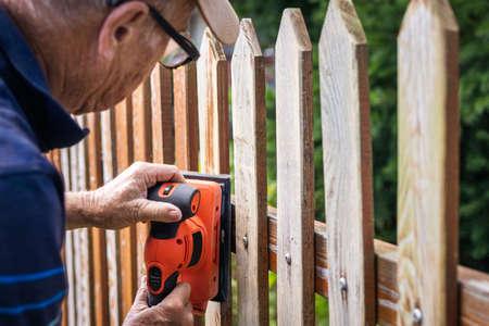 Sanding wooden plank. Senior man grinding picket fence with sander