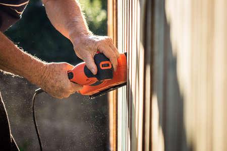 Sander in hands. Sanding wooden picket fence. Electric vibrating power tool grinder
