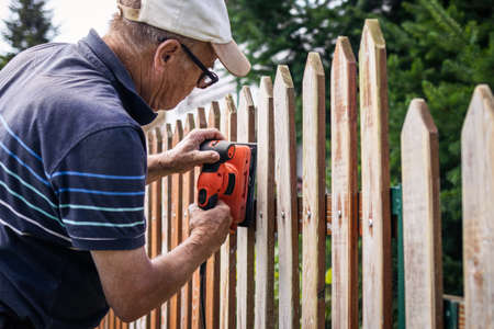 Sanding and preparing wooden fence for painting. Senior man restoring picket fence in garden