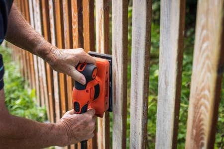 Sanding wooden picket fence. Electric vibrating power tool grinder. Sander in hands