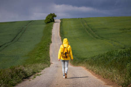 Never knows what is behind the horizon. Lone woman walking on empty road. Exploration, adventure and travel concept