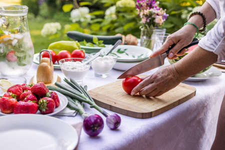 Woman is chopping red tomato on cutting board for vegetable salad. Preparing mediterranean meal for garden party