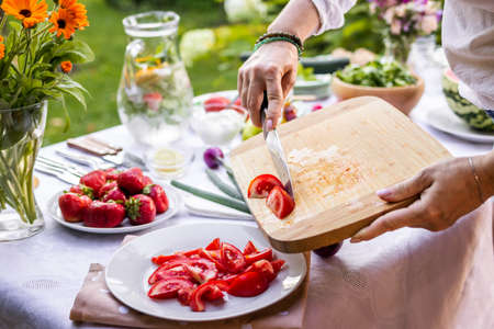 Chopped tomatoes on cutting board. Woman cooking fresh vegetable salad outdoors. Preparing food for garden party
