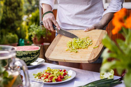 Woman preparing vegetable salad on table. Chopped green bell pepper by kitchen knife on cutting board. Making healthy vegetarian food for summer garden party 免版税图像