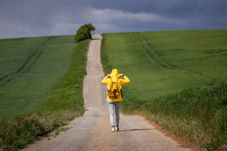 Lone woman walking on empty road. Exploration, adventure and travel concept. female tourist wearing waterproof clothing during spring hike