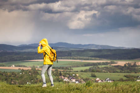Storm and rain is coming. Tourist is wearing waterproof jacket with hood. Woman hiking in rural scenery at spring
