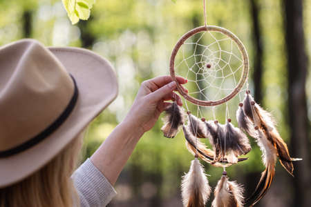 Woman with hat is hanging dreamcatcher in woodland. Indian ritual decoration. Atmospheric mood and spirituality concept 免版税图像