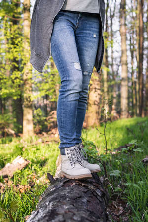 Hiking in the forest. Woman wearing jeans and standing on tree trunk at woodland. Active lifestyle in nature