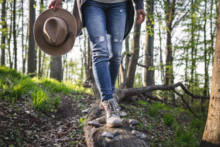 Hiking in the forest. Woman wearing jeans, holding hat and walking on tree trunk. Active lifestyle in nature