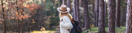 Panoramic view of pine woodland with female tourist person with backpack and hat. Woman hiking in forest alone. Selective focus