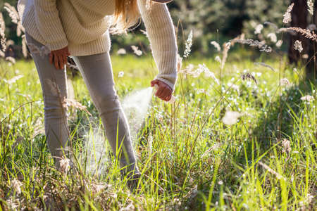 Woman spraying insect repellent against tick at her legs. Protection against mosquito bite during walk in grass