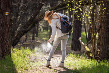 Woman spraying insect repellent against tick at her legs. Protection against mosquito bite during hike in woodland