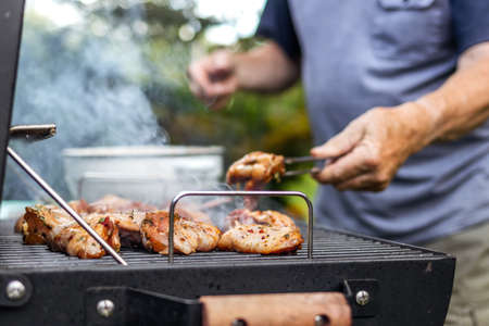 Senior man preparing barbecue grill for garden party. Selective focus at grilled chicken meat