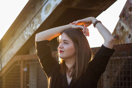 Portrait of attractive young woman in city at sunset. Enjoyment of sunny day. Fashionable brunette woman