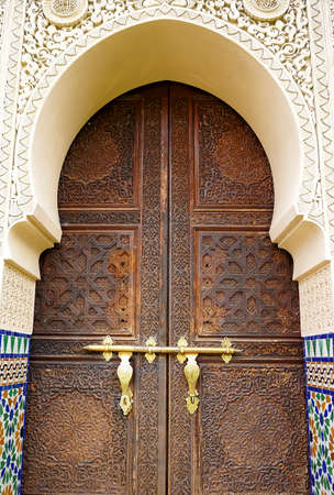Moroccan style door latch on an intricately carved wooden door photo