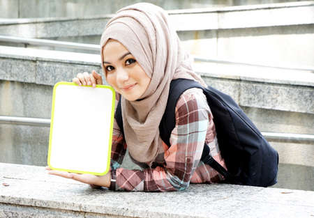 Portrait of a beautiful Muslim woman holding a white board photo