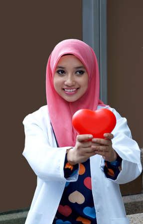Muslim woman doctor holding a plastic heart photo