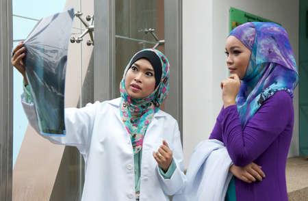 mujeres musulmanas: Mujeres musulmanas j�venes m�dico resultado mirada de rayos x Foto de archivo