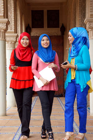 Three beautiful muslim girls having fun talking each other photo