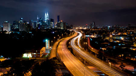 Light trail at busy highway with the view of kuala lumpur city photo
