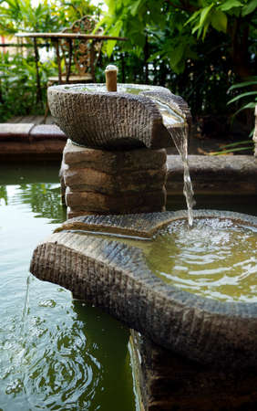 Small decorative fountain on the garden photo