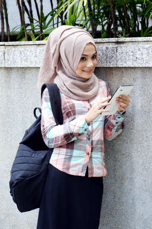 Pretty muslim girl with tablet photo