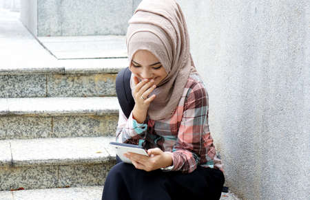 Muslim girl have fun with tablet photo
