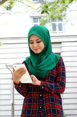 Muslim girl using cell phone or tablet photo