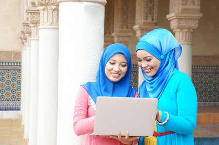 Young Muslim girlfriend with laptop photo