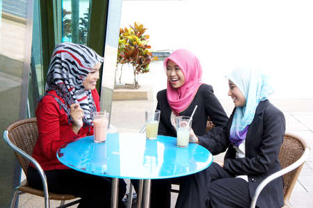 Three muslim girl have fun with their beverage at restaurant