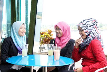 malay food: Muslim girl enjoy having conversation and drink at restaurant