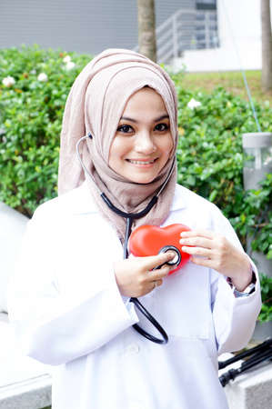A woman doctor holding a heart symbol photo
