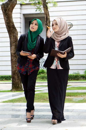 Young muslimah discussing while walking at park photo