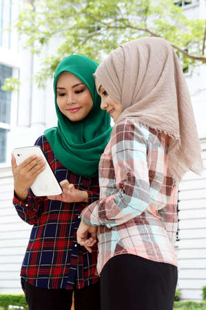 mujeres musulmanas: Mujeres musulmanas compartir informaci�n sobre el trabajo en el parque Foto de archivo