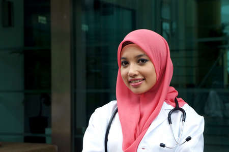 Pretty asian muslim woman doctor smile with stethoscope photo