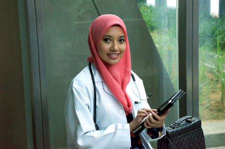Young asian Muslim woman doctor smile with tablet device