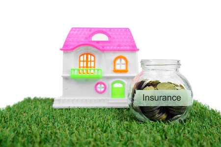 holiday budget: Coins in small container and house toy with label Insurance