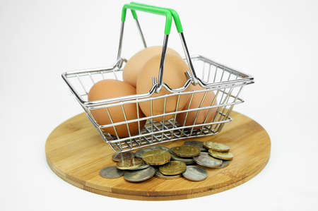 Eggs in small container and shopping cart with coins. financial concept