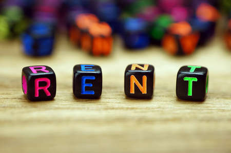 letterpress words: Rent words with dices on wooden table Stock Photo