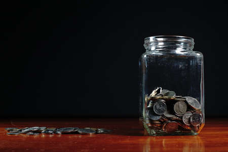penny pinching: Glass jars filled with Malaysian coins against a black background