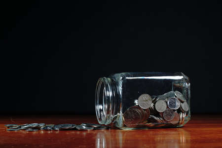 Glass jars filled with Malaysian coins against a black background