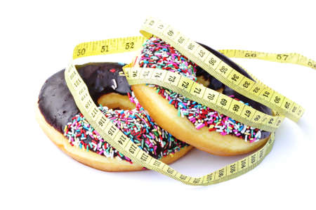 A chocolate frosted donut with colorful sprinkles with a yellow diet measuring tape wrapped around it isolated on a white background  photo
