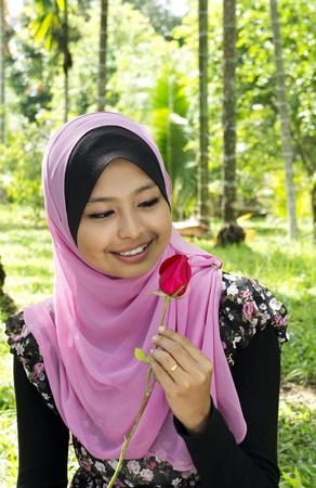 Close-up portrait of beautiful young Asian Muslim woman is holding rose flower