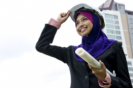 Young Muslim architect-woman wearing a protective helmet standing on the building background
