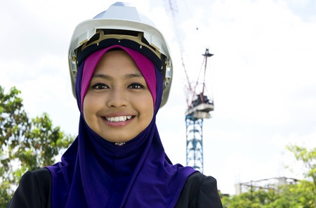 asian architect: Portrait of young Muslim architect-woman wearing scarf with a protective helmet standing on the building background