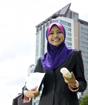 asian architect: Young Muslim architect-woman wearing a protective helmet standing on the building background