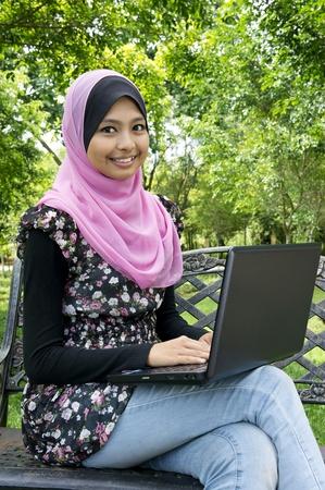 femme musulmane: belle jeune femme asiatique musulmane au parc avec ordinateur portable