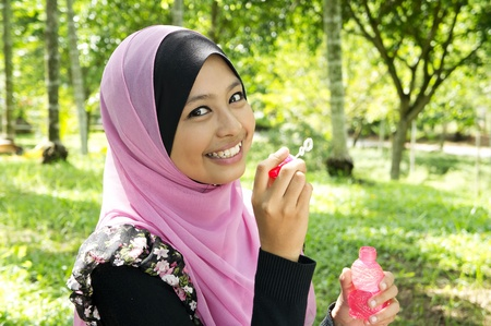a cheerful Muslim woman playing with a soap bubble at park  photo