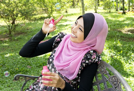 a cheerful Muslim woman playing with a soap bubble at park