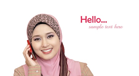 portrait of beautiful young Muslim woman using a mobile phone with a smile on a white background  Stock Photo